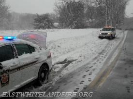 Pennsylvania State Police on Charlestown Road in Charlestown Township with multiple vehicles off the road due to icy conditions.