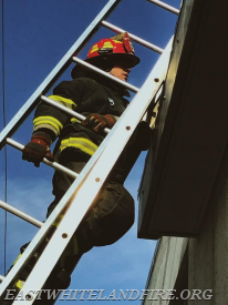 Junior Firefighter Jake Wilson learning ladder techniques. The red helmet signifies junior firefighter.