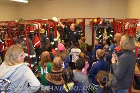 East Whiteland Career Firefighter Brian Garver showing the students a white fire chief's helmet in the gear room.